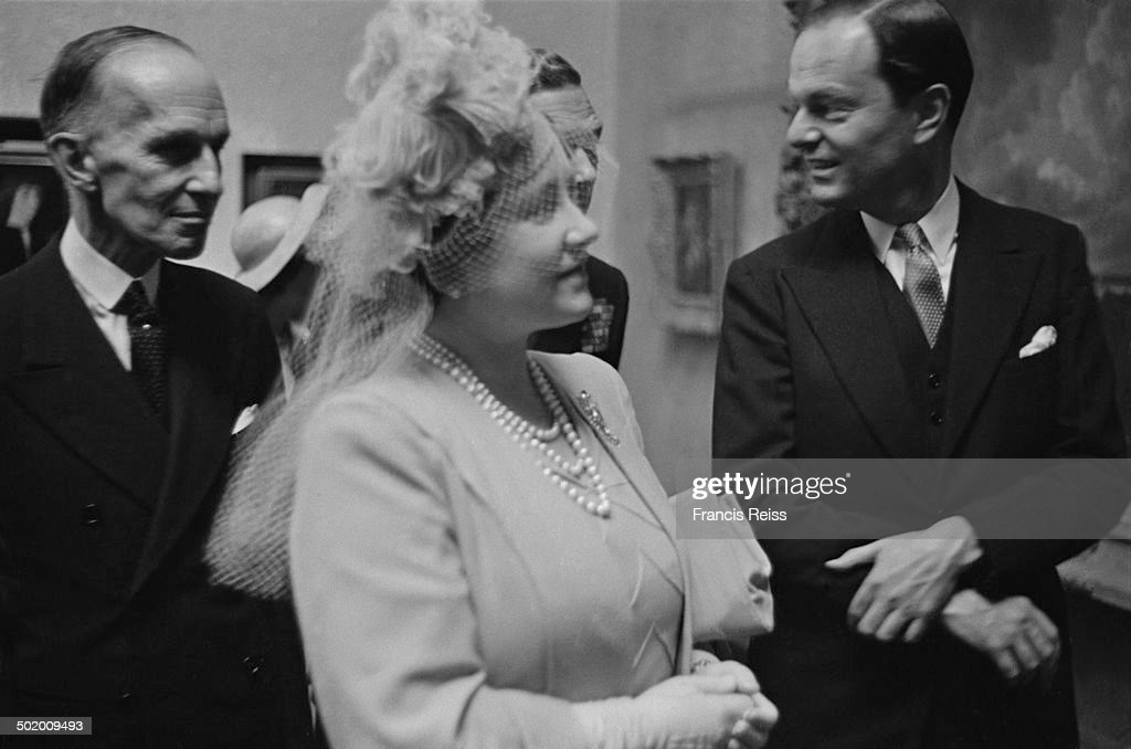 Queen Elizabeth (1900 - 2002, later Elizabeth the Queen Mother) at the National Gallery, London, for an exhibition of works, which had been previously held in storage for the duration of World War II, June 1945. Behind her is King George VI (1895 - 1952). On the right is Sir Kenneth Clarke (1903 - 1983), director of the National Gallery, and on the left is Canadian High Commissioner Vincent Massey (1887 - 1967). Original publication: Picture Post - 1999 - The Pictures Come Back - pub. 9th June 1945