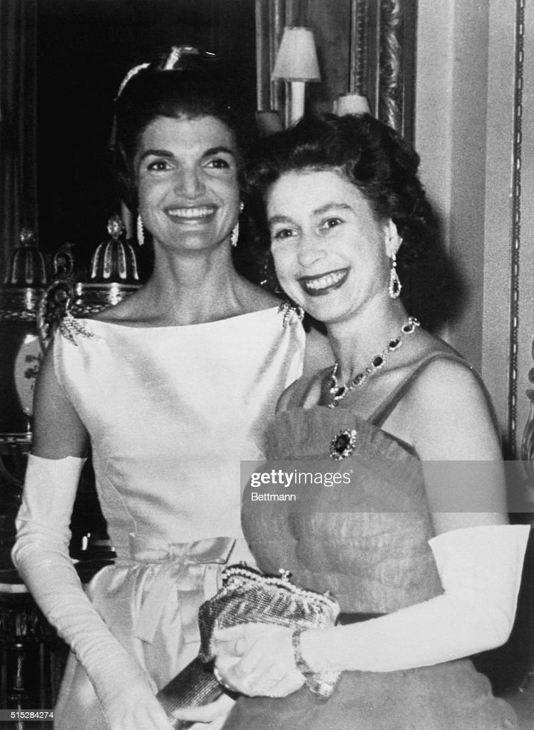Queen Elizabeth (right) flashes a radiant smile as she stands next to Mrs. Jacqueline Kennedy after dinner at Buckingham Palace here June 5th. The U.S. President and the first lady were guests of the Queen and Prince Philip. This was the first time an American President dined at Buckingham Palace since 1918.