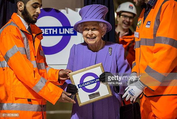 Queen Elizabeth holds a commemorative plaque given to her by Crossrail workers after she formally unveiled the new roundel for the Crossrail line...