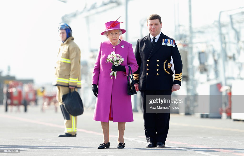 Queen Elizabeth II, accompanied by Captain Timothy Henry, stands on the flight deck of HMS Ocean before departing by helicopter, following a visit to the ship at HM Naval Base Devonport on March 20, 2015 in Plymouth, England.
