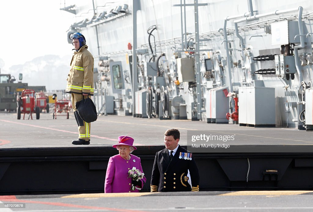 Queen Elizabeth II accompanied by Captain Timothy Henry uses an aircraft lift to reach the flight deck of HMS Ocean before departing by helicopter, following a visit to the ship at HM Naval Base Devonport on March 20, 2015 in Plymouth, England.