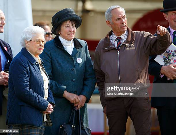 Queen Elizabeth II accompanied by Henrietta Knight and her stud groom Terry Pendry watches her horse 'Tower Bridge' compete in the Cuddy Four Year...