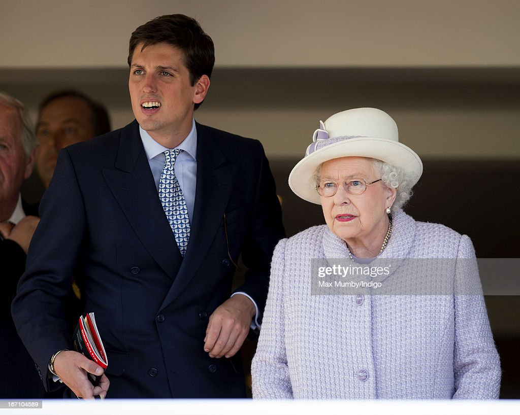 Queen Elizabeth II accompanied by Jake Warren (son of John Warren, Queen Elizabeth II's Racing Manager) watches her horses 'Bold Sniper' and 'Prince's Trust' run in The Dubai Duty Free Tennis Championships Maiden Stakes as she attends the New to Racing Day at Newbury Racecourse on April 20, 2013 in Newbury, England.