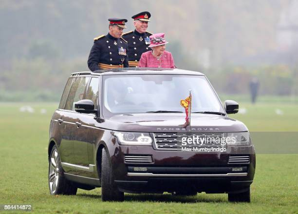Queen Elizabeth II accompanied by Major General Matthew Sykes and Lieutenant General Sir Andrew Gregory stands in her State Review Range Rover to...