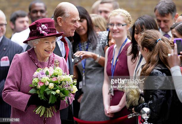 Queen Elizabeth II accompanied by Prince Philip Duke of Edinburgh meets a girl holding a ferret whilst on a walkabout during a visit to City and...