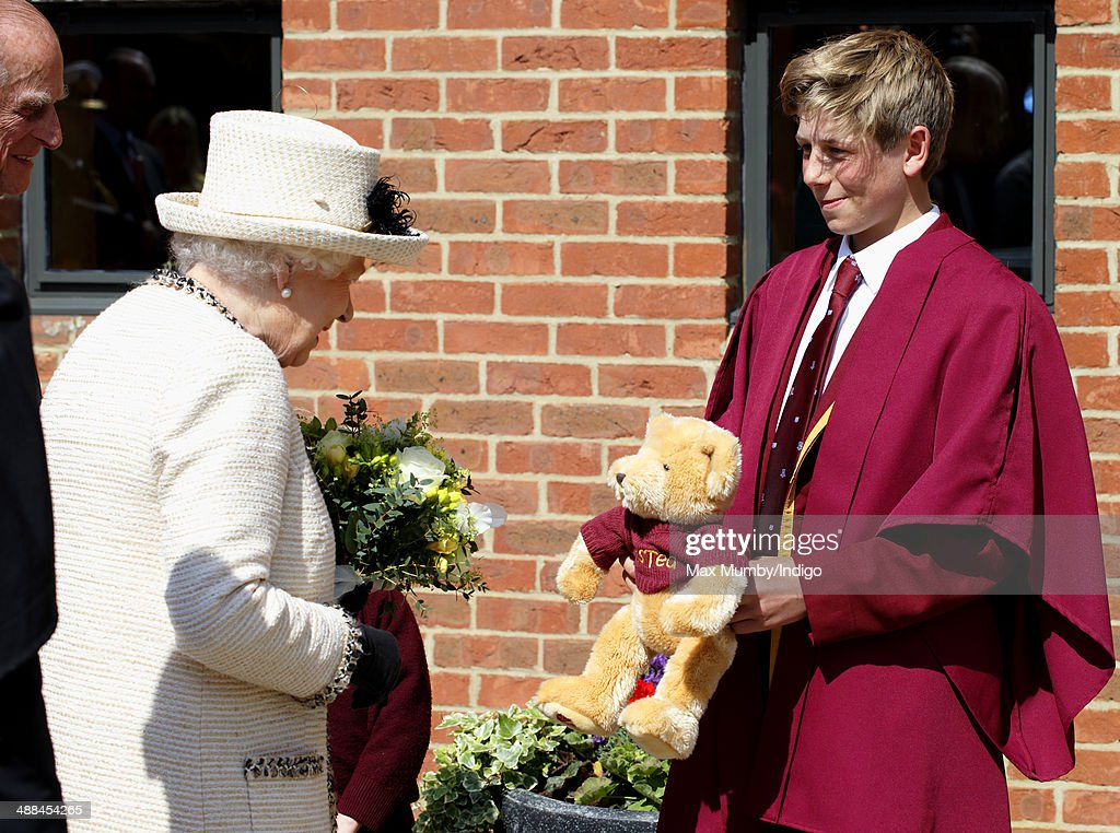 Queen <a gi-track='captionPersonalityLinkClicked' href=/galleries/search?phrase=Elizabeth+II&family=editorial&specificpeople=67226 ng-click='$event.stopPropagation()'>Elizabeth II</a> accompanied by Prince Philip, Duke of Edinburgh is presented with a teddy bear for Prince George of Cambridge as she visits Felsted School during day of engagements in Essex on May 6, 2014 in Felsted, England.