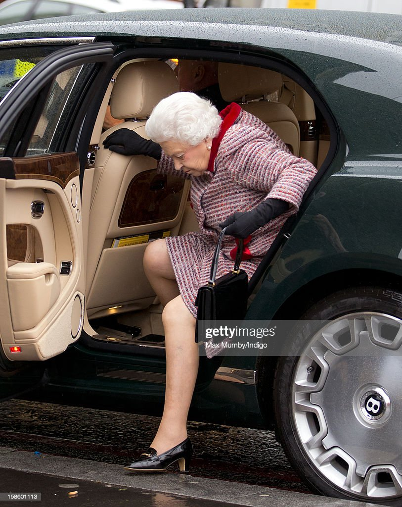 Queen Elizabeth II, accompanied by Prince Philip, Duke of Edinburgh, steps out of her Bentley car as she arrives at King's Cross Railway Station to take the train to King's Lynn on route to her Norfolk Estate, Sandringham House, for her traditional Christmas Break on December 20, 2012 in London, England.