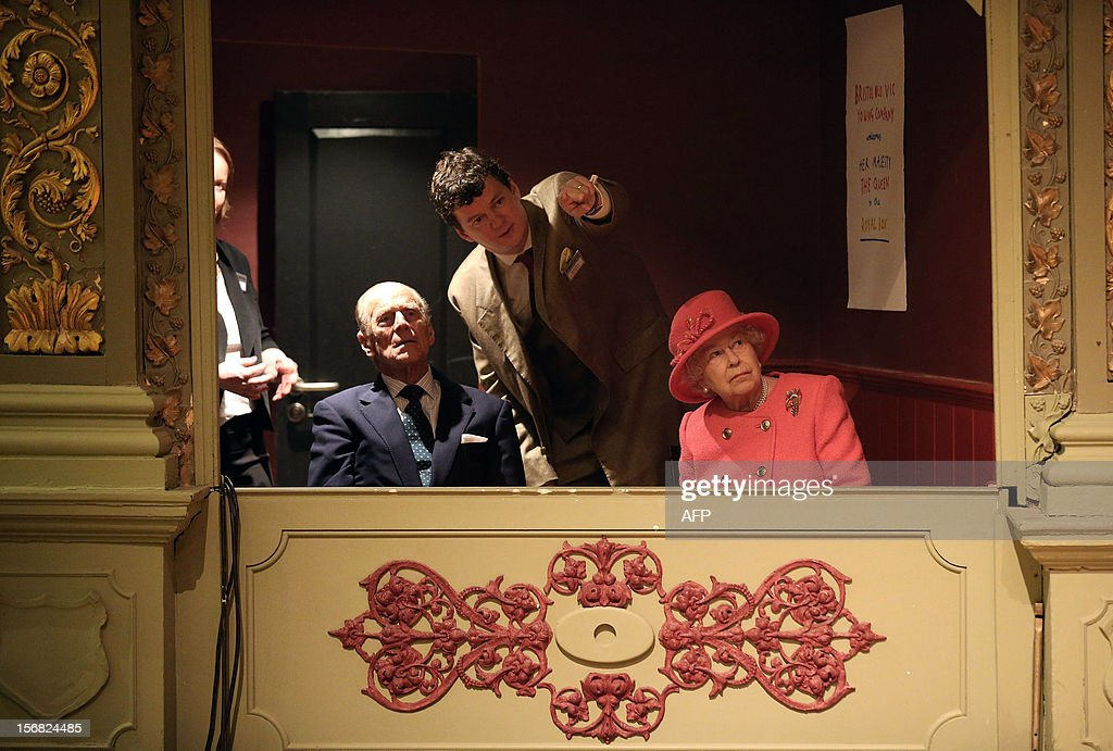 Queen Elizabeth II, accompanied by Prince Philip, Duke of Edinburgh, listen to artistic director Tom Morris as they sit in the Royal Box during a tour of the recently refurbished Bristol Old Vic Theatre on November 22, 2012 in Bristol, England.