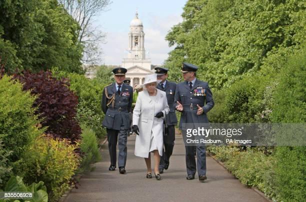 Queen Elizabeth II accompanied by The Duke of Edinburgh and Station Commander Captain Nigel Warmby as she walks along Queens Avenue at RAF Cranwell...