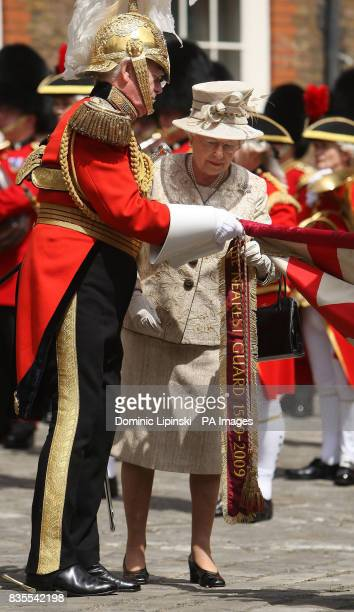 Queen Elizabeth II adds a pendant to the standard of the Gentlemen at Arms in Colour Court at St James's Palace London as part of a parade to mark...