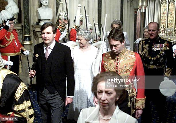 Queen Elizabeth II adjusts her stole as her husband Prince Philip escorts her as she arrives at tThe House of Lords 06 December 2000 in London before...