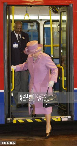 Queen Elizabeth II alights from a double decker bus watched by driver Eugene Collymore at Willesden bus garage North London The Queen was seeing the...