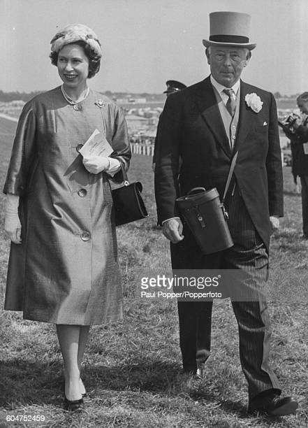 Queen Elizabeth II and Bernard FitzalanHoward 16th Duke of Norfolk walk together down the paddock on the third day of the Derby meeting at Epsom...