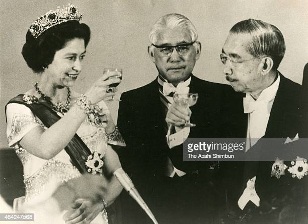 Queen Elizabeth II and Emperor Hirohito toast glasses during the state dinner at the Imperial Palace on May 7 1975 in Tokyo Japan