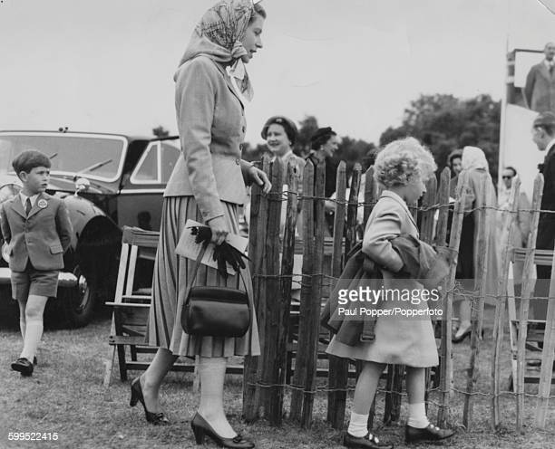 Queen Elizabeth II and her children Prince Charles and Princess Anne arriving at an outdoor event followed by Queen Elizabeth the Queen Mother June...