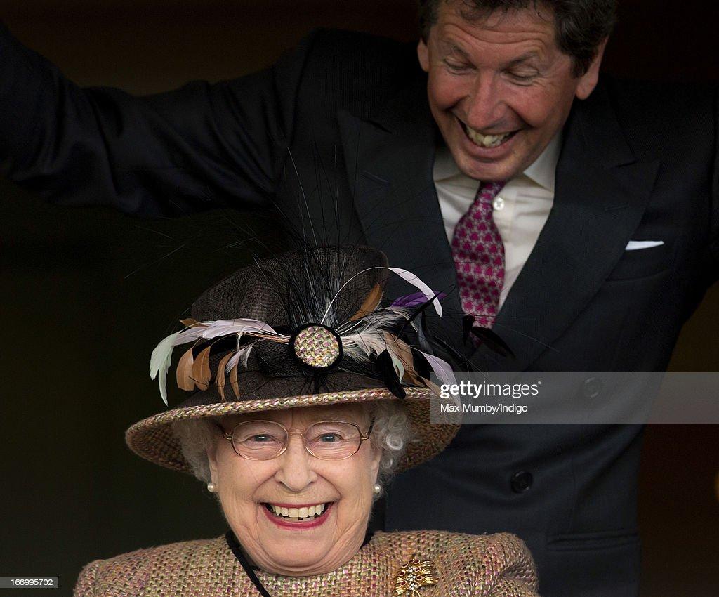 Queen Elizabeth II and her racing manager John Warren watch her horse 'Sign Manual' win The Dreweatts Handicap Stakes at Newbury Racecourse on April 19, 2013 in Newbury, England.