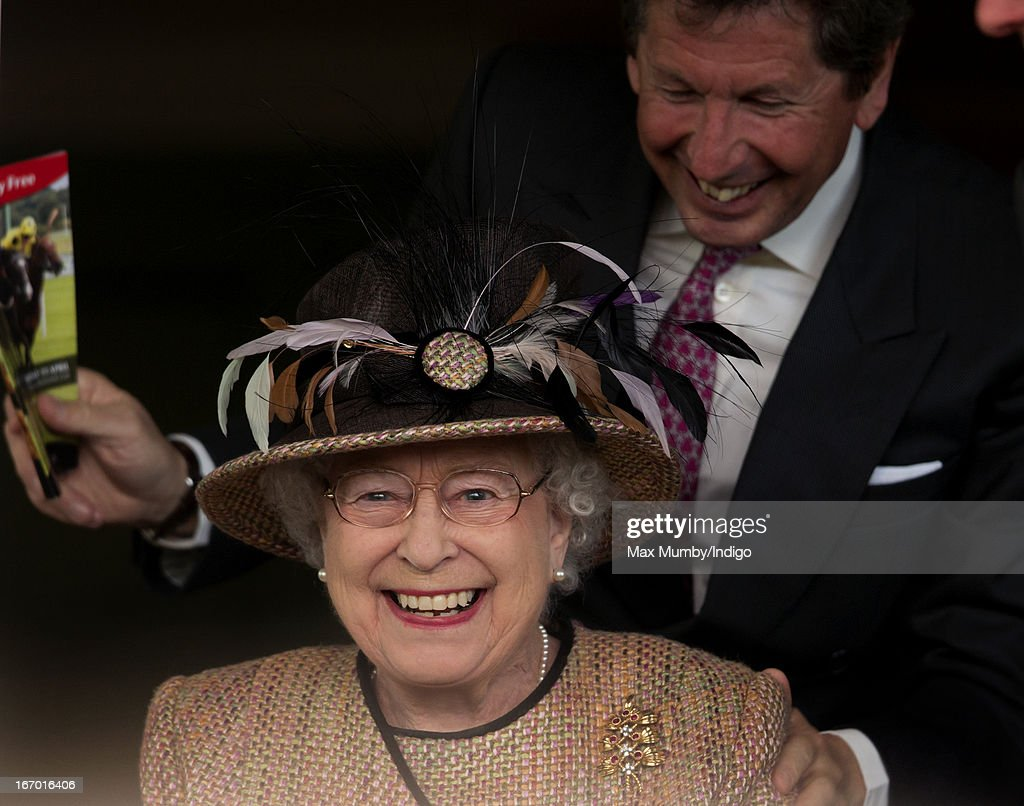 Queen Elizabeth II and her racing manager John Warren watch her horse 'Sign Manual' win the Dreweatts Handicap Stakes as she attends the Dubai Duty Free Raceday at Newbury Racecourse on April 19, 2013 in Newbury, England.