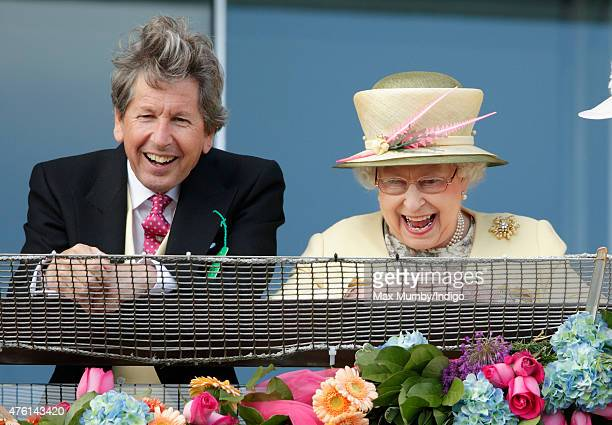 Queen Elizabeth II and her racing manager John Warren watch the racing from the balcony of the Royal Box as they attend Derby Day during the Investec...