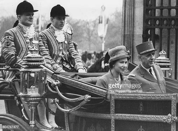 Queen Elizabeth II and President Charles de Gaulle of France ride together in an open Landau carriage as they travel from Victoria Station to...