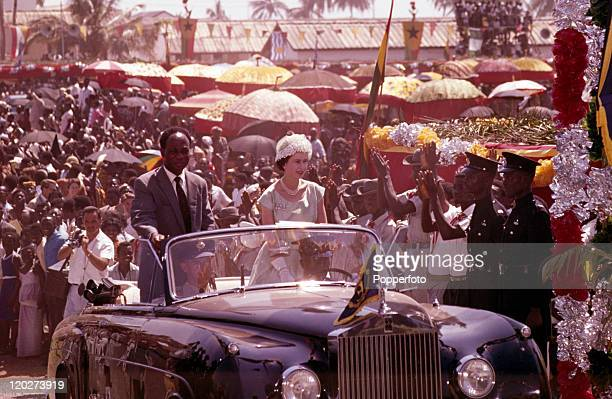 Queen Elizabeth II and President Kwame Nkrumah of Ghana ride in an opentop limousine through cheering crowds in Accra Ghana during the Royal Tour of...