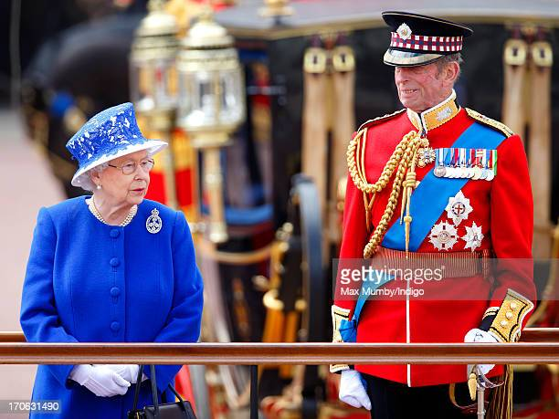 Queen Elizabeth II and Prince Edward Duke of Kent stand on a dais outside Buckingham Palace during the annual Trooping the Colour Ceremony on June 15...