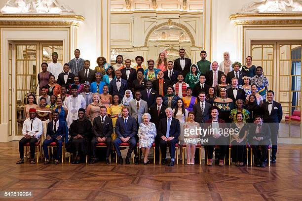 Queen Elizabeth II and Prince Harry sit for a group photo with guests David Beckham and Sir John Major and the sixty winners of the Queen's Young...