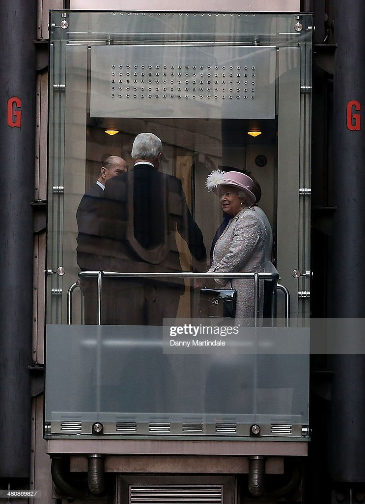 Queen Elizabeth II and Prince Philip Duke of Edinburgh are seen coming down the famous outside lifts as they visit Lloyd's of London to commemorate...
