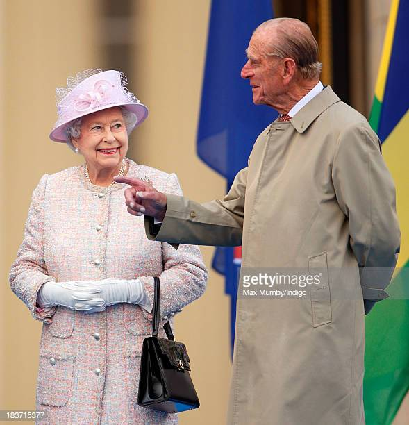 Queen Elizabeth II and Prince Philip Duke of Edinburgh attend the launch of the Queen's Baton Relay at Buckingham Palace on October 9 2013 in London...