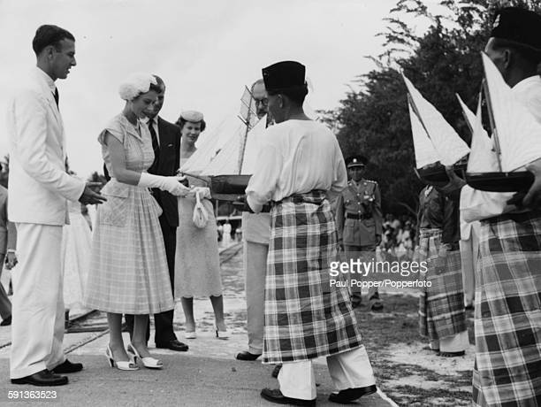 Queen Elizabeth II and Prince Philip Duke of Edinburgh being presented with a model of a Malayan boat by local people during a visit to the Cocos...