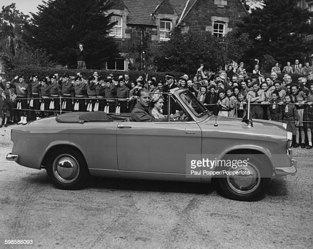 Queen Elizabeth II and Prince Philip Duke of Edinburgh driving a Hillman Minx Convertible LDM 114 Series 1 car past crowds of people during a tour of...
