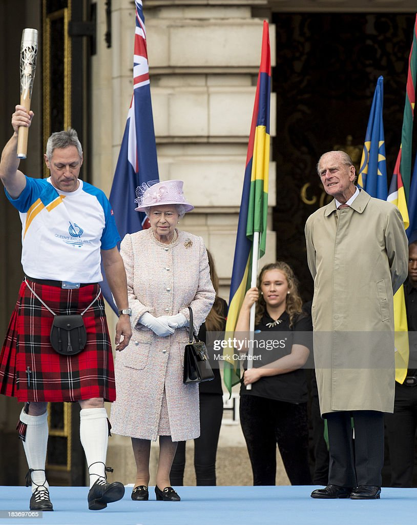 Queen Elizabeth II and Prince Philip, Duke of Edinburgh look on as former Olympic gold medallist Alan Wells carries the baton during the launch of The Baton Relay for the 2014 Commonwealth Games at Buckingham Palace on October 9, 2013 in London, England.