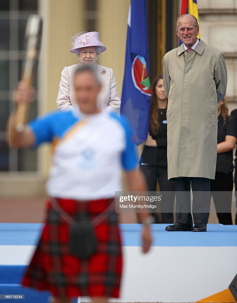 Queen Elizabeth II and Prince Philip, Duke of Edinburgh look on as former Scottish athlete and Olympic gold medalist Alan Wells holds aloft the 2014 Glasgow Commonwealth Baton during the launch of the Queen's Baton Relay at Buckingham Palace on October 9, 2013 in London, England. Following the launch, the baton relay will continue it's journey visiting all 70 competing nations and territories ahead of the 2014 Glasgow Commonwealth Games.