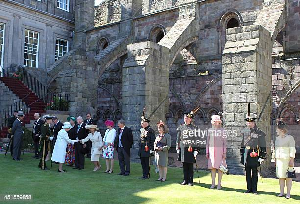 Queen Elizabeth II and Prince Philip Duke of Edinburgh meet guests at a Garden Party at the Palace of Holyroodhouse on July 1 2014 in Edinburgh...