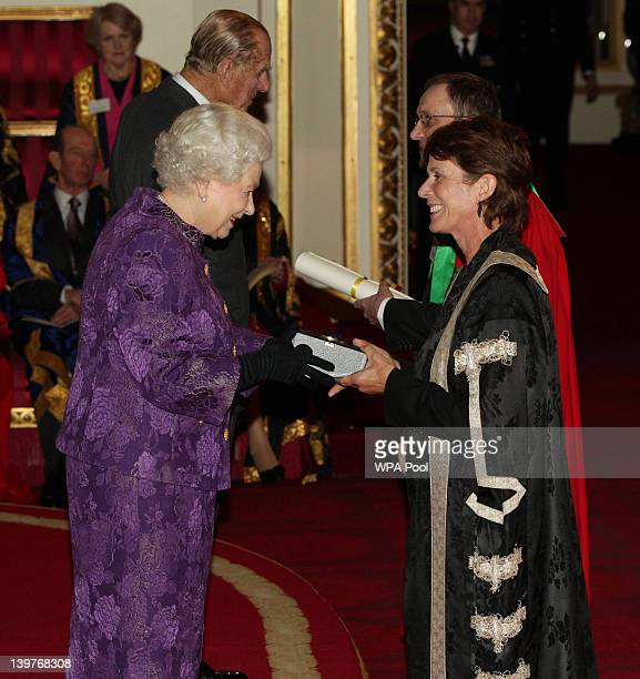 Queen Elizabeth II and Prince Philip Duke of Edinburgh present a Royal Anniversary Prize for Higher and Further Education to Professor Louise...