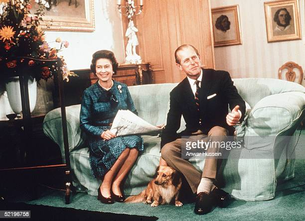 Queen Elizabeth II and Prince Philip Duke of Edinburgh relax with their corgis and a newspaper at Balmoral Castle in 1974 in Balmoral Scotland