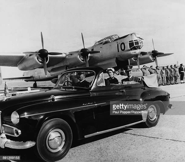 Queen Elizabeth II and Prince Philip Duke of Edinburgh sit together in the back of an open car as they pass by lines of aircraft including an...