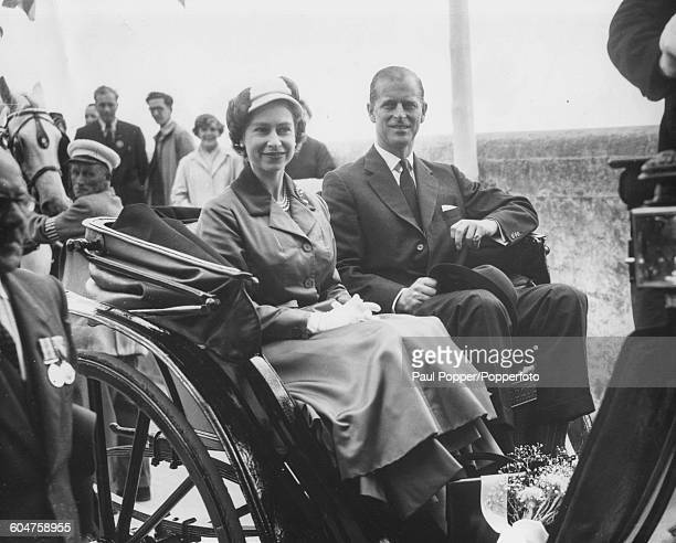 Queen Elizabeth II and Prince Philip Duke of Edinburgh sit together in a Victorian carriage driven by John A de Carteret as they leave the harbour...