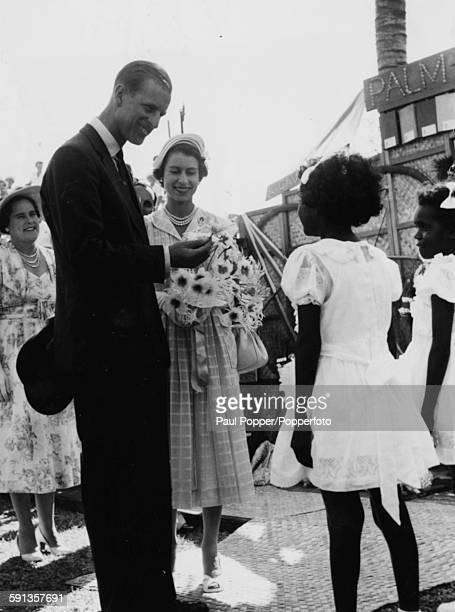 Queen Elizabeth II and Prince Philip Duke of Edinburgh talk with two aboriginal children Nita Longden and Meralyn Gunnawarra who presented Her...