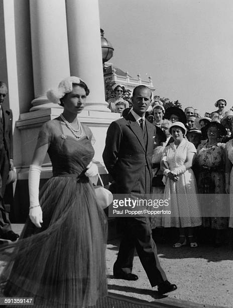 Queen Elizabeth II and Prince Philip Duke of Edinburgh walk past crowds of spectators as they make their way to the Royal Tea Marquee during a garden...