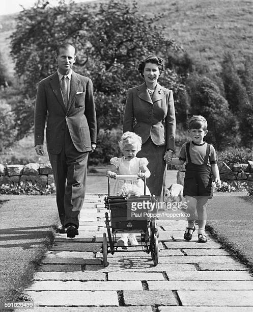 Queen Elizabeth II and Prince Philip Duke of Edinburgh walking with their children Prince Charles and Princess Anne pushing a toy pram in the grounds...