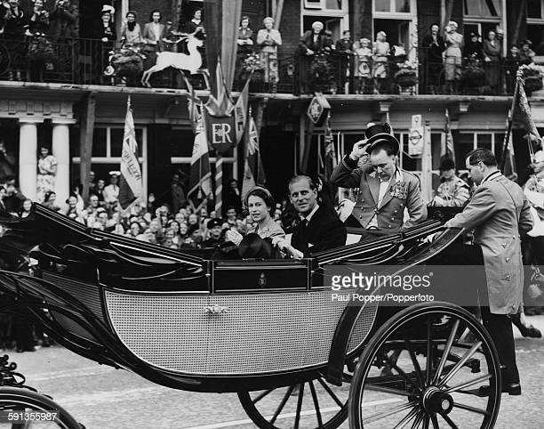 Queen Elizabeth II and Prince Philip Duke of Edinburgh wave from an open carriage as they drive through crowded streets past the White Hart hotel in...