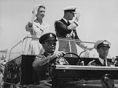 Queen Elizabeth II and Prince Philip Duke of Edinburgh wave from an open car to crowds lining the streets of Valetta after her majesty unveiled a war...