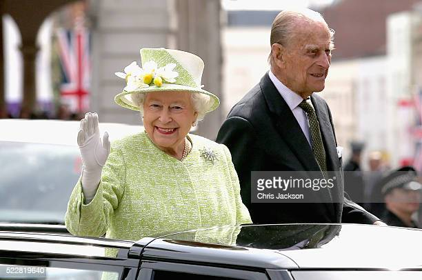 Queen Elizabeth II and Prince Philip Duke of Edinburgh wave from the top of an open Range Rover on the monarch's 90th Birthday on April 21 2016 in...