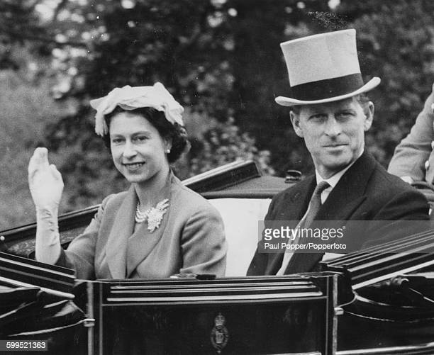 Queen Elizabeth II and Prince Philip Duke of Edinburgh wave from the Royal Carriage as they arrive for a race meeting at Ascot Racecourse England...