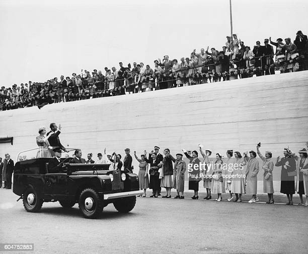 Queen Elizabeth II and Prince Philip Duke of Edinburgh wave to crowds of spectators from the back of an open top Land Rover car as they drive along...