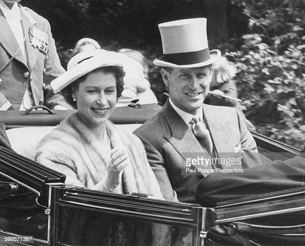 Queen Elizabeth II and Prince Philip Duke of Edinburgh waving from the Royal Carriage as they arrive at Ascot Racecourse for the second day of the...