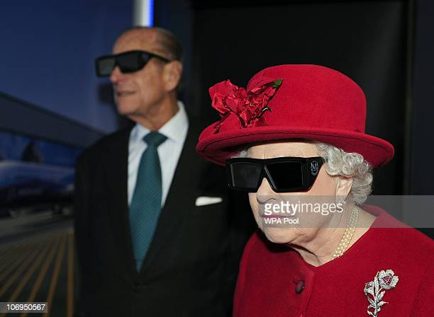 Queen Elizabeth II and Prince Philip Duke of Edinburgh wear 3 D glasses to watch a display and pilot a JCB digger during a visit to the University of...