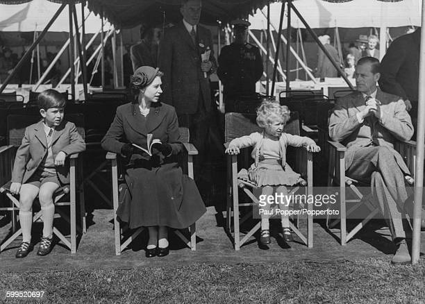 Queen Elizabeth II and Prince Philip Duke of Edinburgh with their young children Prince Charles and Princess Anne all sitting in lawn chairs as they...
