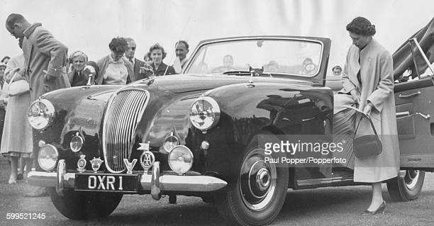 Queen Elizabeth II and Prince Philip getting in to their 3 litre Aston Martin Lagonda DHC convertible car after a polo match at Cowdray Park in West...
