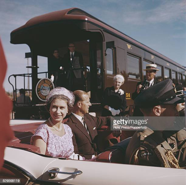Queen Elizabeth II and Prince Philip Mountbatten Duke of Edinburgh pictured sitting in the back seat of an open top car in Whitehorse Yukon during...
